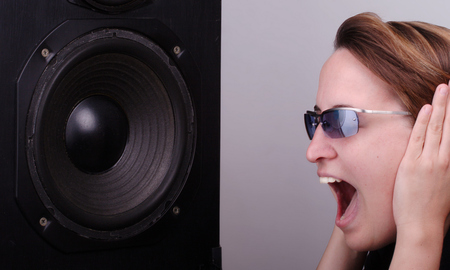 Young woman shouting in front of speaker box