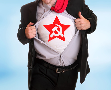 Young angry businessman tearing his shirt communist symbol hammer and sicke on it
