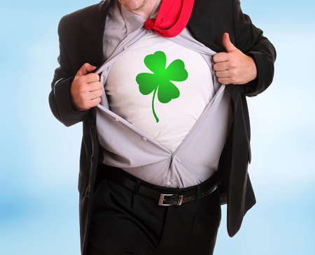 Young angry businessman tearing his shirt four-leaf clover symbol on it