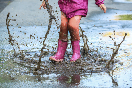 Playful child outdoor jump in puddle in boot after rain