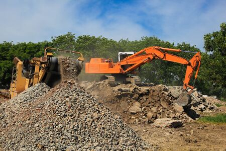 Stone crusher and crane in working Stock fotó