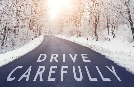 Empty road in forest in winter with drive carefully text