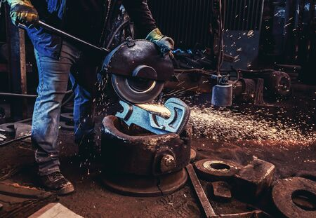 Worker cut metal with angle grinder