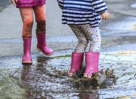 Playful children outdoor jump into puddle in boot after rain Stok Fotoğraf