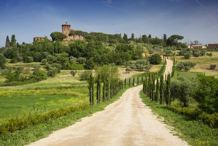 Beautiful landscape in Tuscany with road, castle and cypress trees, Italy.