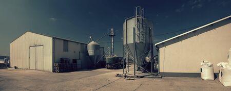 Modern farm buildings with silos and tractor 版權商用圖片