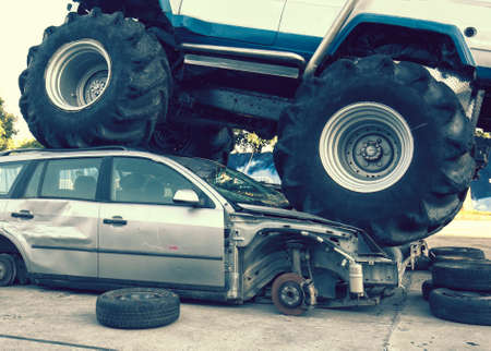 Monster truck wrecked car on road