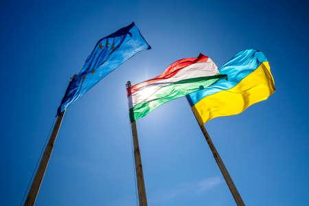 Flags of Hungary Ukraine and European Union waving on pole against blue sky
