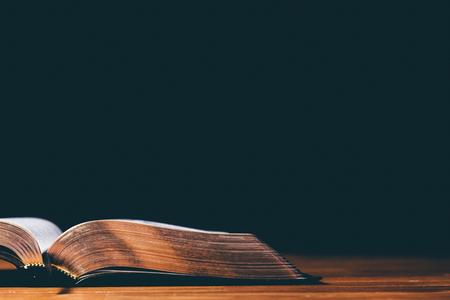 Öffnen Sie Bibel auf schwarzem Hintergrund Standard-Bild