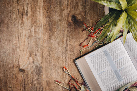 Open bible on a wooden table whit a blanket and a plant. Top view flat lay. Standard-Bild
