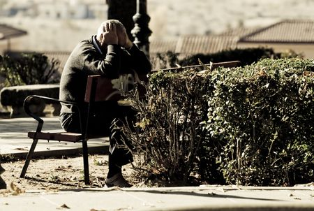 An old man in a bench, worried for his problems. photo