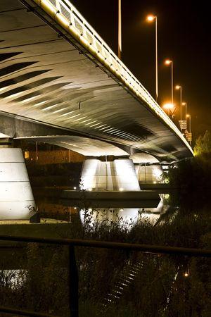 a nocturne: Night concrete bridge across the river . Stock Photo