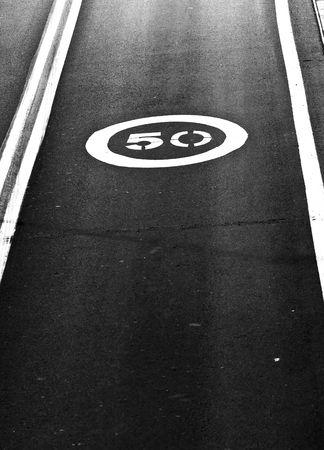 slower: Speed limit printed on the asphalt Stock Photo