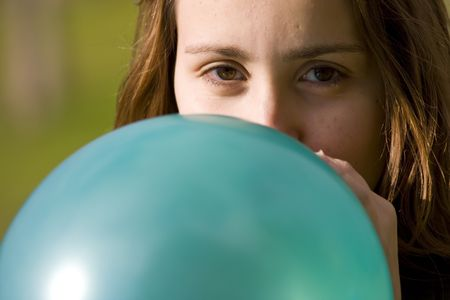 Closeup on woman inflating blue balloon photo