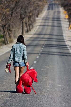 runaway: Young woman lefted behind with her teddy bear. Stock Photo