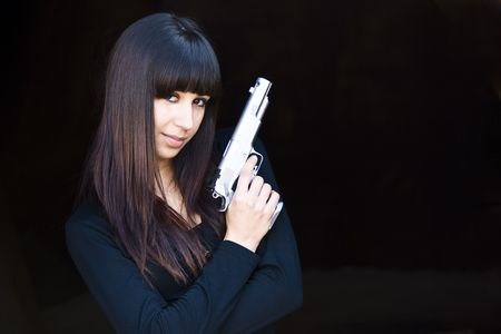 Attractive woman posing with pistol against black background photo