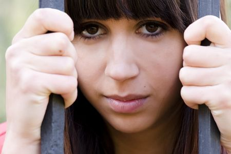 wistful: Young woman portrait in jail. Stock Photo