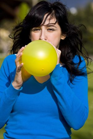 inflating: Teen inflating yellow balloon