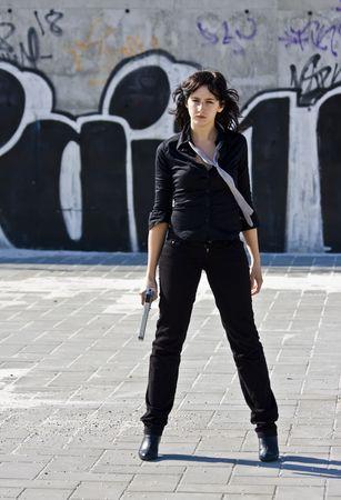 barrel pistol: Mafia girl in urban graffiti background