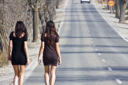 parade: Two young women walking on the road