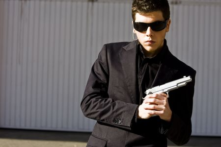 special service agent: Male model performing secret agent with gun Stock Photo