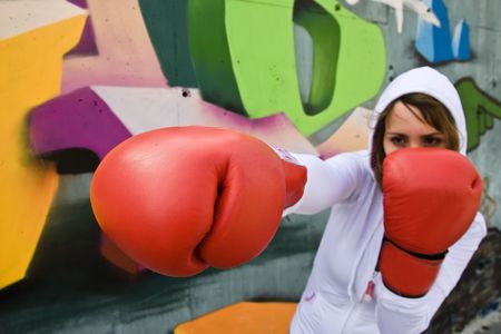 graffiti background: Boxing woman over graffiti background, focus on glove.