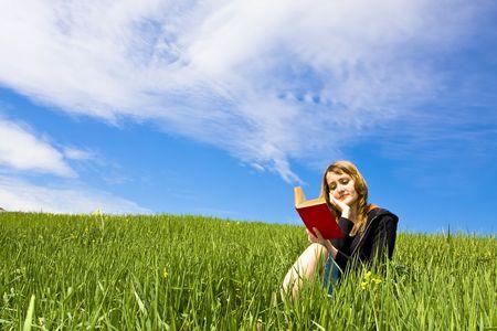 잔디 위에 읽는 금발의 여자