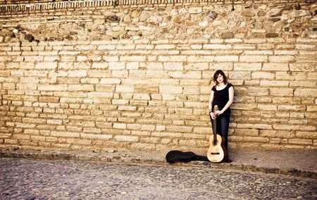 Street artist standing with her guitar on the wall photo