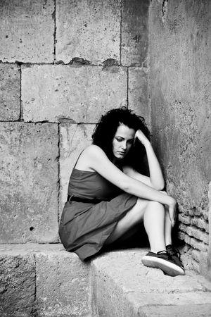 Sad jonge vrouw in een hoek Stockfoto