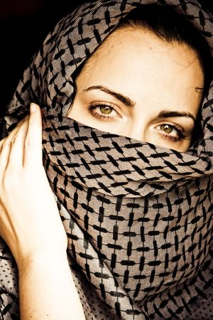Green eyed beauty with her face covered. photo