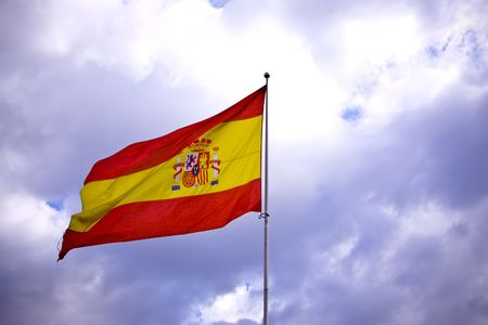 flagpoles: Spanish flag over stormy clouded sky.