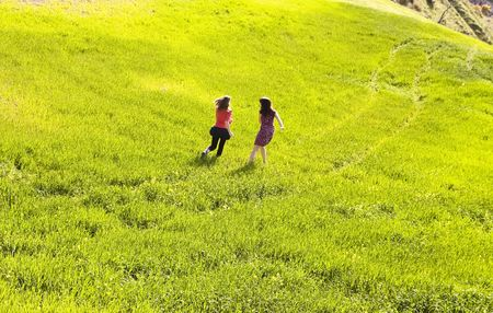 Couple of friends running down the meadow photo