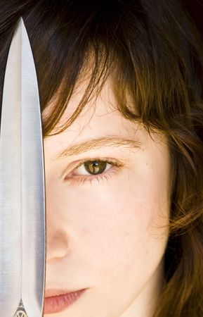 Young blond woman with a knife over her face Stock Photo