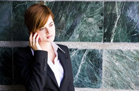 Beautiful businesswoman at phone over marble background. photo