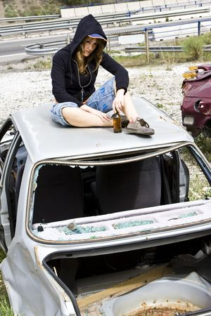 wreckage: Young woman taking beer in the scrapyard Stock Photo