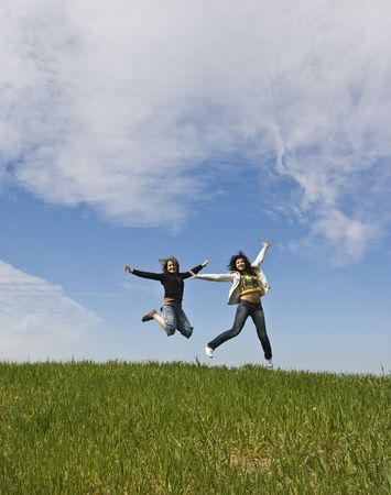Young friends jumping on green meadow photo