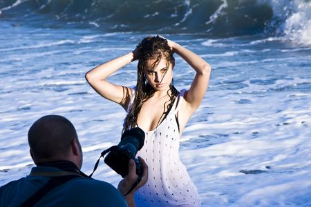 Young beautiful model posing wet on the beach photo