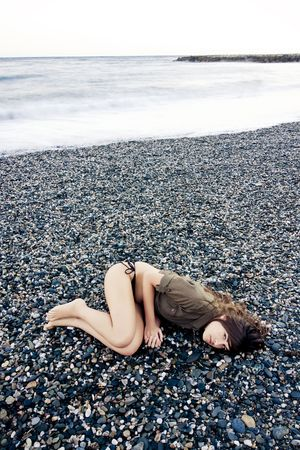 Beautiful woman laying on the beach with sad gesture. Long exposed waves. photo