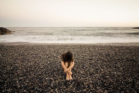 Young sad woman alone in a black stone beach. photo