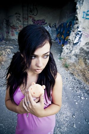 Young little girl with her teddy bear lost in a dirty place photo