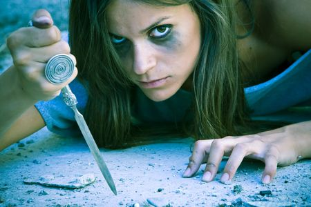 hate: Violent dark woman armed with a knife Stock Photo