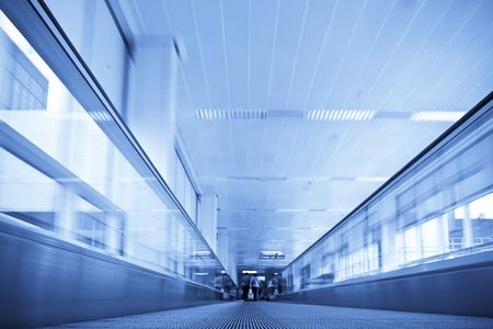 rushing hour: Moving in walkway along blue corridor. Stock Photo