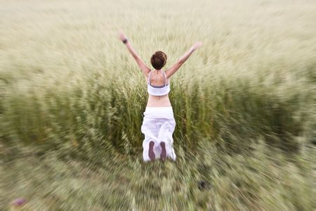 Young blond woman jumping in meadow. photo