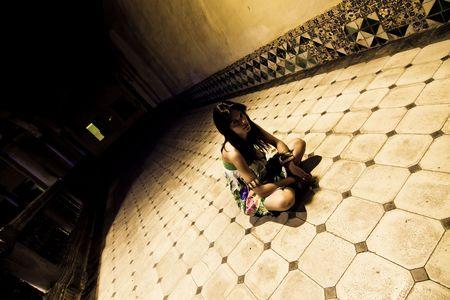 sanitarium: Young woman sited on the sanitarium floor.