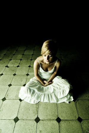 Young beautiful woman surrounded by darkness photo