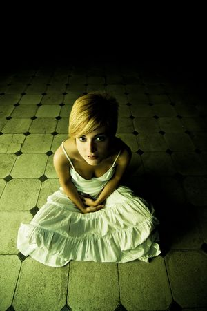 Young beautiful woman surrounded by darkness Stock Photo