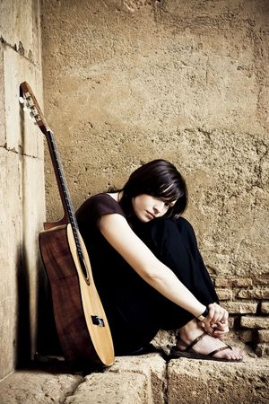 sandalias: Lone triste guitarrista situados en el antiguo brickwall.  Foto de archivo