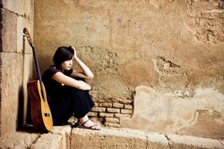 Lone sad guitarist sited in old brickwall.