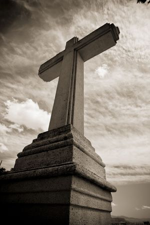 Christian stone cross under blue sky photo