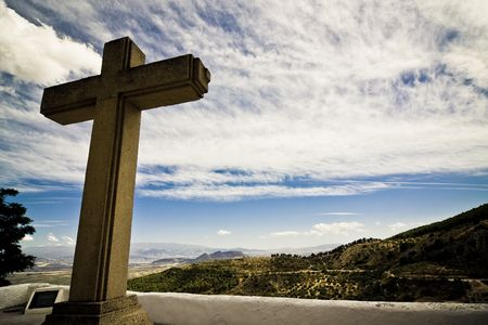 dramatically: Christian cross in Mediterranean landscape, dramatically toned. Stock Photo